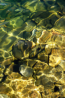 Emerald colored rocks and pebbles supported by an intricate light play on the surface of a pristine lake at the Grand Teton National Park in Wyoming.