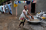 """Romage Jean Louis, 11, seen here washing dishes at her home, is a Peace Pal in the southern Haitian village of Mizak. Peace Pals is a program of the World Peace Prayer Society, which promotes the message """"May Peace Prevail on Earth"""" as a simple, universal expression to unite the hearts of all people in a common desire and hope for peace on Earth. Peace Pals provides a safe and nurturing environment for children to gather to play and learn lessons that organizers hope will lead to generational changes in attitudes about self-worth, care for the environment, personal health & hygiene, conflict resolution, respect for all persons and encouragement to be """"peacebuilders"""" at all levels. In Mizak, Peace Pals is sponsored by Haitian Artisans for Peace International (HAPI)."""