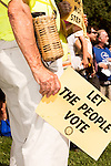 July 13, 2015. Winston Salem, North Carolina.<br />  A rally member awaits the start of the march to support the NC NAACP's voting rights case against Gov. Pat McCrory.<br />  To rally support for the North Carolina NAACP's case against Gov. Pat McCrory (NC NAACP v. McCrory), a march was held in downtown Winston Salem on the opening day of the case in federal court. Thousands gathered to walk the streets of downtown and listen to speeches proclaiming the importance of defeating new requirements for voter registration,<br />  The NC NAACP contests that HB 589 (Voter ID requirements) violate Section 2 of the Voting Rights Act (42 U.S.C. 1973) and the Fourteenth and Fifteenth Amendments of the Constitution.