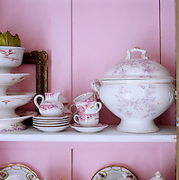 The pink-and-white colour scheme used for the dining room cupboard has been picked out from the collection of antique porcelain it houses