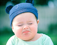 Young toddler boy wearing a hat in the summer sun with a cute frown as he begins to cry
