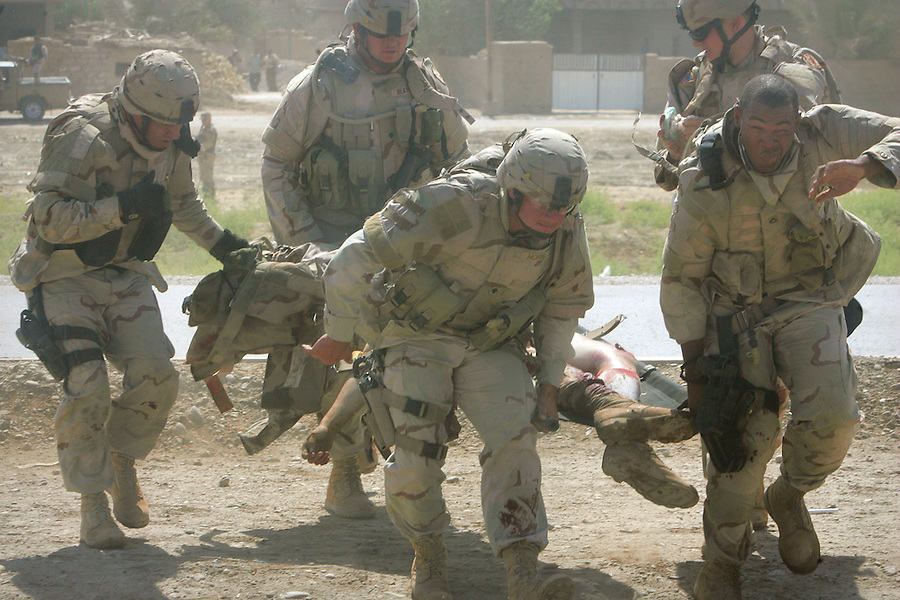 Comrades of US soldier gravely wounded when an IED was detonated under his Humvee on June 19, 2005 carry him toward a waiting medevac helicopter from the 50th Medical Company (Air Ambulance) 101st Airborne Division out of Camp Taji, Iraq for the flight to the 86th Combat Support Hospital in Baghdad's Green Zone.