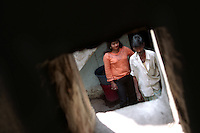 INDIA (West Bengal - Calcutta) -A sex worker waits in a lane while a customer passes by. Kolkata, India- Arindam Mukherjee