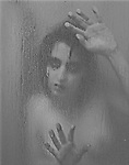 Portrait of a demon like woman through a glass with her hands against it, looking creepy.