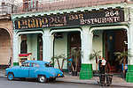 Havana, Cuba; a blue classic 1950's Chevy, parked in front of the Prado 264 restaurant, along the Paseo de Marti in the late afternoon