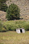 Leaning wooden outhouse and derelict houses and buildings in the ghost town of Russell in the Sangre de Cristo Range