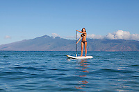 An athletic, fit woman standup paddling at Napili Bay, Maui, with Molokai in the distance.