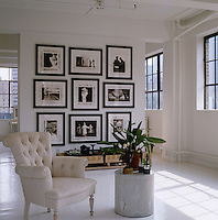 Framed black and white photographs mounted on the partition wall are in stark contrast to this otherwise all-white living room