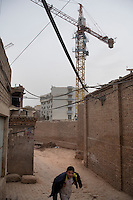 Cranes hover above the Old City of Kashgar, Xinjiang, China.