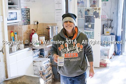 Happy tiling student with mug of tea, Able Skills, Dartford, Kent.
