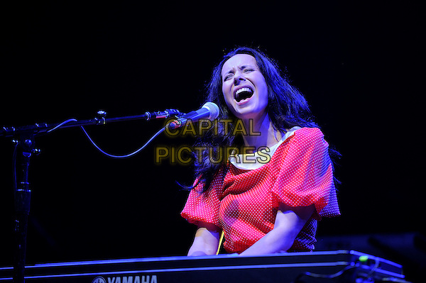 Nerina Pallot <br /> performing in concert, LG Arena, Birmingham, England, UK, <br /> 21st September 2013.<br /> music live on stage gig half length singing microphone playing keyboard red dress  <br /> CAP/MAR<br /> &copy; Martin Harris/Capital Pictures