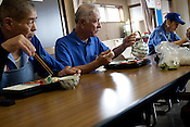Elderly workers eat lunch from their bento-box lunch, which the company provides at a cost to each worker of JPN Yen 300, at Kato (a light industry company) in Nakatsugawa, Japan, Monday 21st June 2010. Kato company has a workforce of 100 people, 50% of whom are 60 years of age or older. The elderly work force earn JPN &yen;800-1,000 per hour, but receive no annual bonus or pay rise.