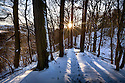 Late afternoon sun bursting through snow-covered woodland in Winter. Peak District National Park, Derbyshire, UK. Seasons sequence 2 of 2.
