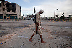 A barefoot revolutionary fighter walks away from the front line where pro-Gaddafi snipers took up positions to target revolutionary fighters in central Sirte, Libya, Oct. 13, 2011. Revolutionary forces solidified control of the pro-Gaddafi stronghold, but fighting continued in a few neighborhoods.