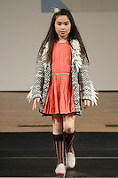 Model walks runway in an outfit by Velveteen, during the petitePARADE Children's Club fashion show at the Jacob Javits Center in New York City, on January 9, 2016.