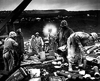 Across the litter on Iwo Jima's black sands, Marines of the 4th Division shell Jap positions cleverly concealed back from the beaches.  Here, a gun pumps a stream of shells into Jap positions inland on the tiny volcanic island. Ca. February 1945. (Coast Guard)<br /> Exact Date Shot Unknown<br /> NARA FILE #:  026-G-4122<br /> WAR &amp; CONFLICT #:  1219
