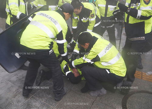 Ferry tragedy protest, Apr 18, 2015 : Policemen check one of their colleague policemen injured as they block protesters trying to march toward Gwanghwamun gate near the presidential Blue House in Seoul, South Korea. About 30,000 people  (8,000 by police estimate) demonstrated on April 18,  two days after the first anniversary of Sewol ferry tragedy to demand that the government scrap the special Sewol Law enforcement decree, salvage the ferry and hold a thorough investigation into the tragedy. They also called for resignation of President Park Geun-hye.The police detained about 100 protesters during the protest. (Photo by Lee Jae-Won/AFLO) (SOUTH KOREA)