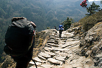 Trekkers navigate the stone trail on their way towards Namche Bazaar in Nepal. Everyone trekking in the Khumbu region will visit Namche Bazaar. The village is the gateway to the high Himalaya and has many internet cafés, shops, and lodges.