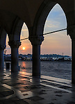 The sun rising between the column of the portico of Palazzo Ducale (Doge's Palace) in Venice, Italy