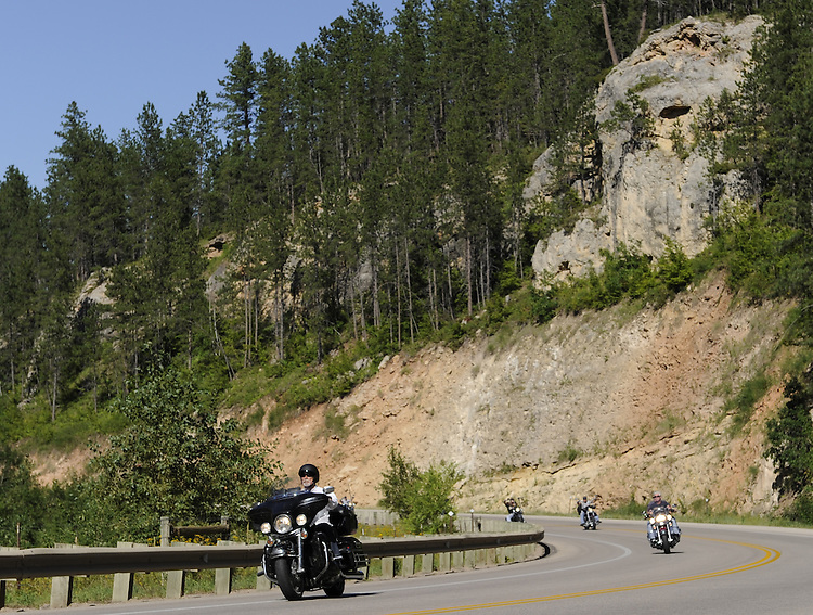 STURGIS, SOUTH DAKOTA - AUGUST 2010:  Motorcyclists ride on Highway 14 in the Black Hills of South Dakota while attending the 70th annual Sturgis Motorcycle Rally.  The attendance estimates were placed between 500, 000 and 700,000 bikers.