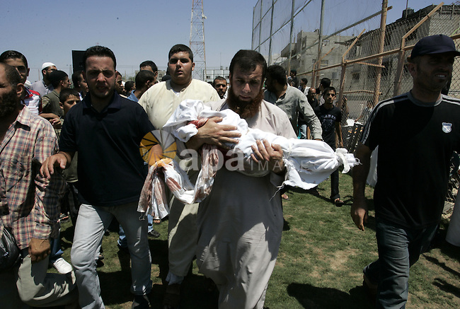 A Palestinian man carries the body of two-year-old boy Malek Sha'at during his funeral in Rafah in the southern Gaza Strip August 19, 2011. Israeli fighter jets bombed Gaza, killing a teenager and injuring five people, in retaliation to a series of coordinated attacks on August 18 near the southern Israeli sea resort of Eilat that left eight dead. Photo by Abed Rahim Khatib