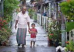 Ahman Yani walks with his 3-year old son Arabil in Kuala Bubon, in Indonesia's Aceh province. The community of 118 houses was built by the ACT Alliance after the village's tsunami survivors refused to accept government plans to relocate them inland far from the sea. After the houses were built, the community then successfully fought a government plan to demolish part of the new village to make way for a new highway.