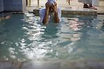 Joma Sanir submerges himself in water during evening prayers at the Mandean temple in Basra, Iraq, May 16, 2010. The Mandean religious sect, with practices drawn from the time of John the Baptist, requires moving water such as a river for their religious rites. The Basra Mandeans use an indoor water tank, because the canal outside the temple is too polluted. Flow of the Shatt al Arab river, which runs from Qurna to the Persian Gulf and feeds Basra's canals, has been cut drastically by dams in Syria, Turkey and Iran.