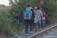 Illegal migrants leave the railway racks to evade police detention after they passed an opening on the razor wire fence on the border between Hungary and Serbia near Roszke (about 174 km South of capital city Budapest), Hungary on September 01, 2015. ATTILA VOLGYI