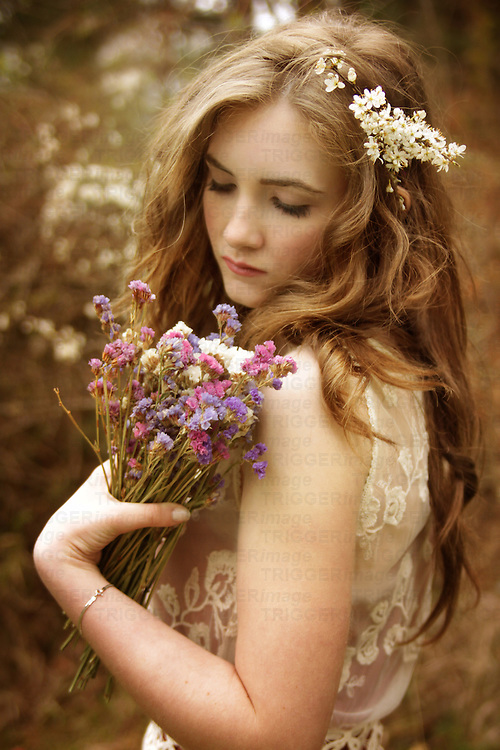 A young girl with pale skin and long blond hair holding a bouqet of wild spring flowers