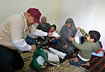 Saad Gedeon (left), the program coordinator for International Orthodox Christian Charities in Jordan, distributes hygiene kits to a Syrian refugee family in Amman. The family of eight fled the city of Homs as fighting there worsened in 2012. Their home in Syria has since been destroyed by bombing, and they are struggling to survive in Jordan's capital city. The IOCC is a member of the ACT Alliance. The hygiene kits include a towel, soap, toothbrush, comb, and other items.