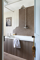 A panel of marble provides a splash back for the old-fashioned shower above the deep cast enamel bath in the bathroom