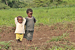Children stand alongside a farm field where their mother is working at an agricultural school sponsored by the United Methodist Committee on Relief (UMCOR) in Kaminsamba, Democratic Republic of the Congo. Participants, some of whom stay at the center for several weeks, learn sustainable agricultural practices, animal traction, and beekeeping.