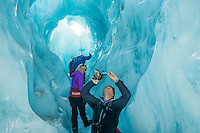 Tourists ejoying guided walk through amazing blue ice tunnel, cave on Franz Josef Glacier, Westland National Park, West Coast, World Heritage Area, South Westland, New Zealand