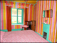 BNPS.co.uk (01202 558833)<br /> Pic: PhilYeomans/BNPS<br /> <br /> 2nd Bedroom.<br /> <br /> Britain's wackiest property has come on the market...And the estate agents mantra of paint everything magnolia has definately not been applied.<br /> <br /> It may look like an idyllic cottage in the Forest of Dean from the outside but ceramic artist Mary Rose Young's unique taste has transformed the interior into what looks like something from Alice in Wonderland.<br /> <br /> The three-bedroomed house is decorated from head to toe in crazy colours, clashing patterns, and enormous murals,<br /> each room is covered in the garish designs, including the bathroom, where even the sink and toilet have been adorned in bright tiles.<br /> <br /> Estate agents Bidmead Cook now have the tricky task of showing prospective punters round the &pound;500,000 property.