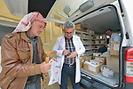 Yusef Gorges, a 66-year old internally displaced Christian, gets a prescription filled by Pharmacist Aodeshu Yanan during the visit of a mobile clinic to the village of Sharafiya, Iraq, which was flooded with displaced families when the Islamic State group took over nearby portions of the Nineveh Plains in 2014. The clinic is a program of the Christian Aid Program Nohadra - Iraq (CAPNI). Inside the vehicle is Pharmacist Aodeshu Yousif. Yanan was also displaced by ISIS.