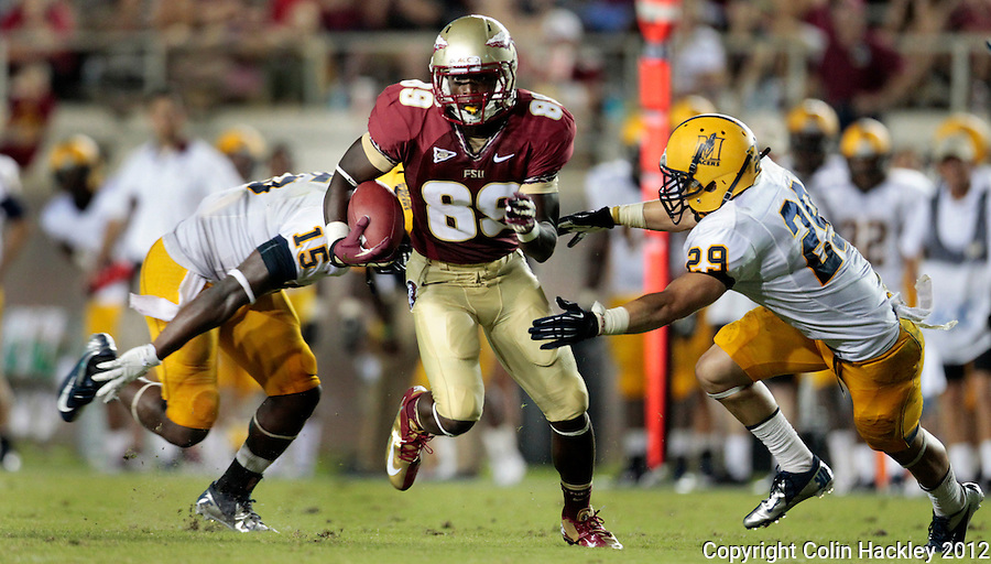 TALLAHASSEE, FL 9/1/12-FSU-MURRAY090112CH-Florida State's Christian Green runs between Murray State's Qua Huzzie, left, and Darian Yahyavi during second half action Saturday at Doak Campbell Stadium in Tallahassee. The Seminoles  beat the Racers 69-3..COLIN HACKLEY PHOTO