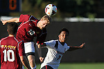 30 August 2013: Elon's Nathan Diehl (19) heads the ball over Northeastern's Nikko Lara (7). The Elon University Phoenix played the Northeastern University Huskies at Koskinen Stadium in Durham, NC in a 2013 NCAA Division I Men's Soccer match. The game ended in a 1-1 tie after two overtimes.