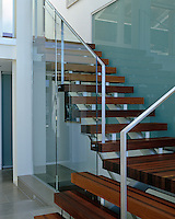 An open-plan staircase of steel and laminated walnut has a glass partition that acts as a safety barrier
