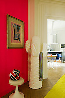 Vibrant accents of colour can be found all over the apartment as shown in this hallway where a dayglo yellow rug covers the parquet floor beside a vermilion-painted wall