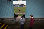 Port Talbot Town 3 Caerau Ely 0, 06/02/2016. Genquip Stadium, Welsh Cup fourth round. Two young spectators watching the first-half action as Port Talbot Town (in blue) play host to Caerau Ely in a Welsh Cup fourth round tie at the Genquip Stadium, formerly known as Victoria Road. Formed by exiled Scots in 1901 as Port Talbot Athletic, they competed in local and regional football before being promoted to the League of Wales  in 2000 and changing their name to the current version a year later. Town won this tie 3-0 against their opponents from the Welsh League, one level below the welsh Premier League where Port Talbot competed, watched by a crowd of 113. Photo by Colin McPherson.