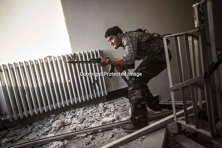 In this Tuesday, Oct. 30, 2012 photo, a rebel fighter belonging to the Liwa Al-Fatah takes cover as he aims on his enemy position from a school building during skirmishes with the Syrian army in the nearby Bustan Al-Pasha front line in Aleppo, Syrian's largest city. (AP Photo/Narciso Contreras).