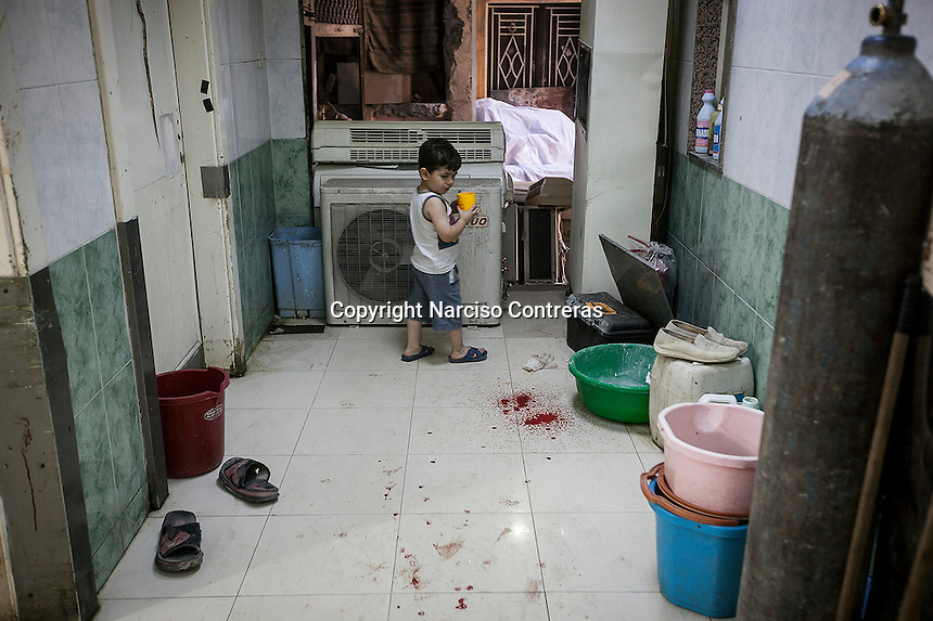 Omar, four-year-old, looks to a puddle of blood as he walks through the emergency ward corridor at the Dar Al-Shifa hospital, located in the rebel-controlled area of Aleppo, Syria. September 26, 2012.
