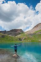 Female hiker balances on rock in Ice Lake, Ice Lakes basin, San Juan mountains, Colorado, USA