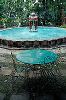 Fountain and wrought iron table in the Jardin Borda, Cuernavaca, Morelos, Mexico. The 18th-century Borda Garden was the summer residence of Emperor Maximilian and Empress Carlota.
