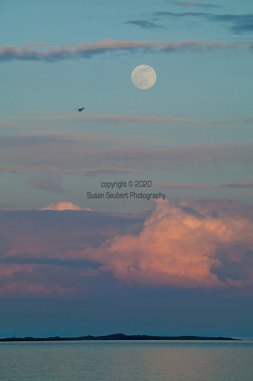 The view of a sea plane and the rising full moon from Dallas Road.