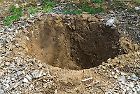 Digging a hole in the ground showing soil