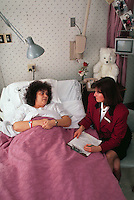 A female doctor or health care worker visits with a patient at her bedside in a hospital.