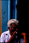 In Matanza a man smokes a cigerette waiting for a political meeting with his neighbors to discuss possible income ideas.