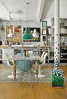 An open plan kitchen/dining room with a beamed ceiling, painted brick walls and a wood floor. A green pendant light hangs above a breakfast table with Eero Saarinen and Harry Bertoia chairs.