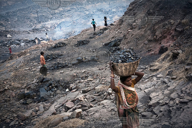 Women and children carrying out coal from an open cast mine near Bokapahari village. Coal fires rage just below the surface of the ground, making it too hot to walk with naked feet. Noxious gases spew up from fissures, rendering the environment toxic. Residents who live above the furnace make $2 a day collecting small chunks of coal that they sell to illegal middlemen. One or two houses collapse annually into vast underground caverns left unfilled by abandoned mining operations.